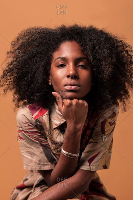 Serious African American model with Afro hairstyle leaning on hand and looking at camera on brown studio background