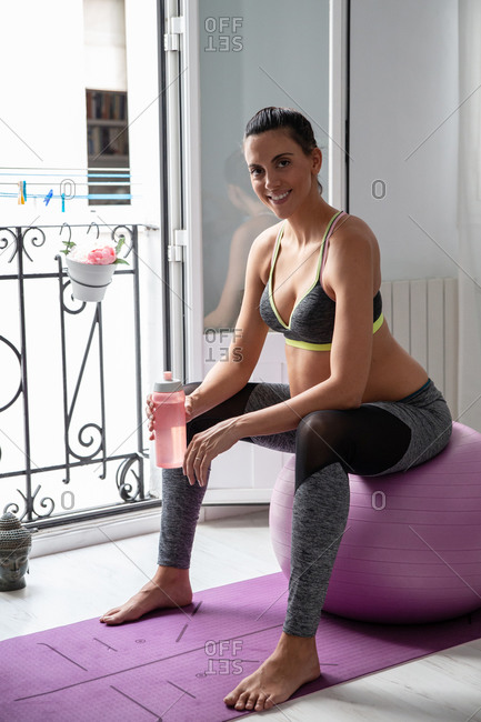Tired happy pregnant female in sportswear sitting on fit ball with bottle of water and resting after doing yoga at home looking at camera