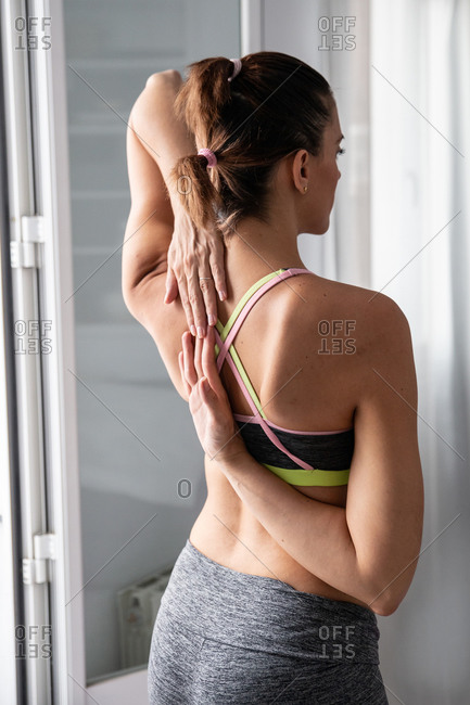 Back view of slim female in bra and leggings standing with hands behind back and doing yoga at home