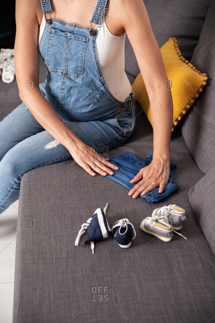 From above of unrecognizable pregnant female sitting on couch with baby apparel and sneakers at home