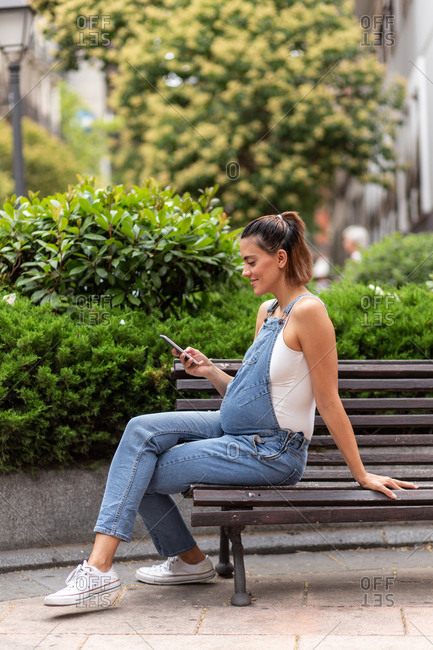 Side view of calm happy pregnant female sitting on wooden bench in street and browsing mobile phone
