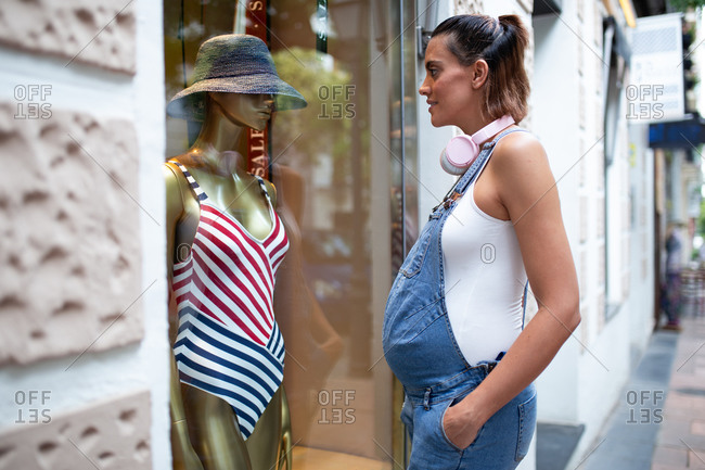 Side view of pregnant female looking at slim dummy in swimsuit placed behind glass case of store while dreaming about summer vacation