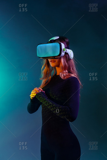 Young unrecognizable blonde woman standing wearing virtual reality headset on colorful blue neon illumination studio background