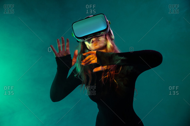 Young unrecognizable blonde woman standing touching air and wearing virtual reality headset on colorful blue neon illumination studio background