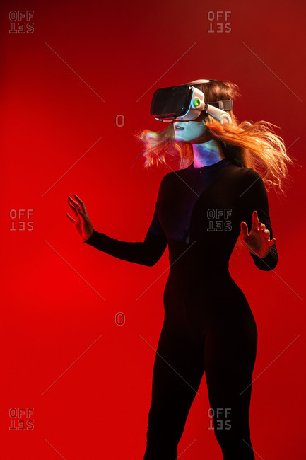 Side view of young unrecognizable blonde woman standing touching air and wearing virtual reality headset on colorful red studio background