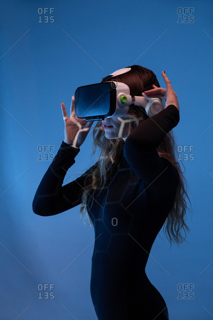Side view of young unrecognizable blonde woman standing wearing virtual reality headset on colorful blue studio background