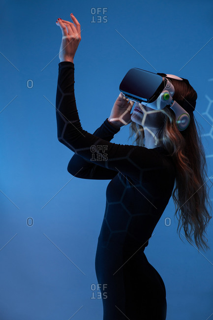 Side view of young unrecognizable blonde woman standing touching air and wearing virtual reality headset on colorful blue studio background