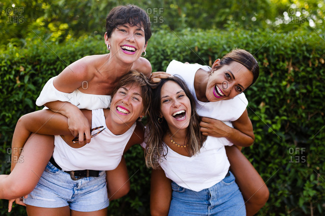 Delighted women piggybacking female friends and laughing on street while having fun and enjoying weekend together