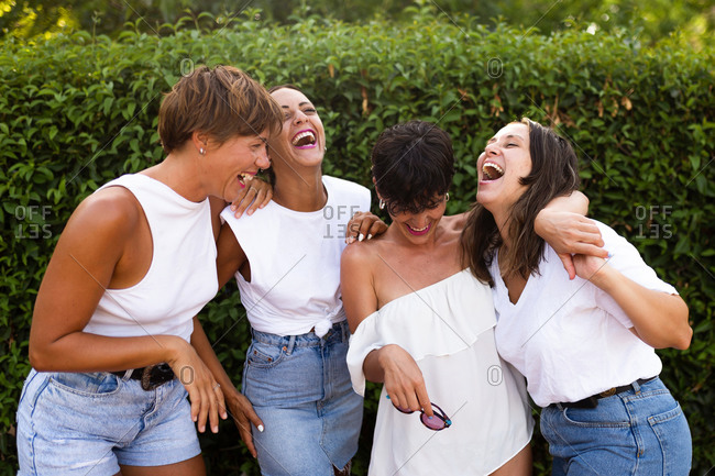 Group of carefree friendly women hugging together and having fun while standing in city and laughing at joke