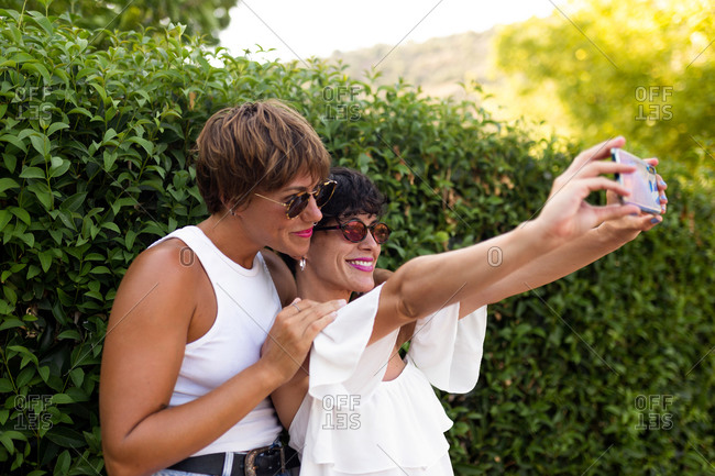 Side view of stylish adult female friends standing near green shrubs in park and taking selfie on smartphone while spending summer weekend together