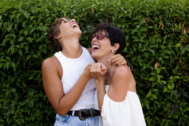 Adult friendly women cuddling in green park while smiling sincerely