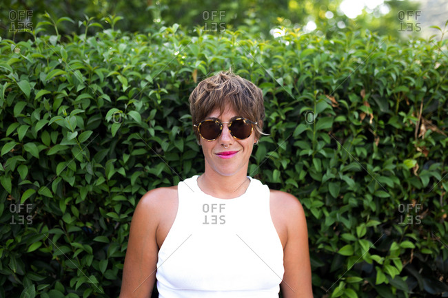 Content adult female with short hair and in trendy outfit standing in green park in summer and looking at camera