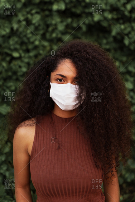 Young black female in protective mask and with curly hair standing in urban park and looking at camera during coronavirus epidemic