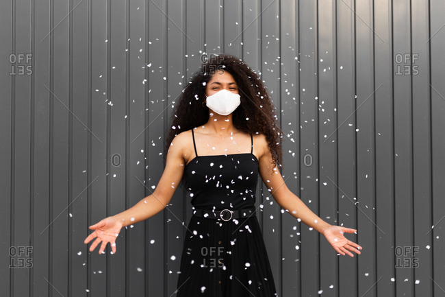 Joyful African American female with curly hair and mask scattering white confetti in city while having fun and looking at camera