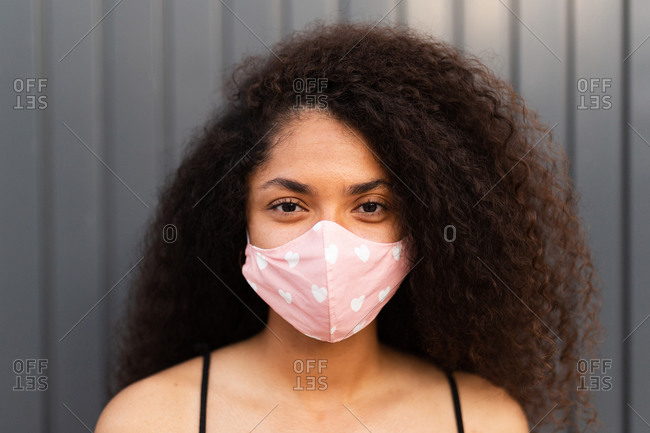 Positive African American female with curly hair wearing pink protective mask standing near urban building in city during coronavirus pandemic and looking at camera