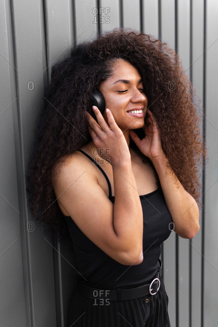 Lovely African American female with long curly hair and headphones in city and closed eyes