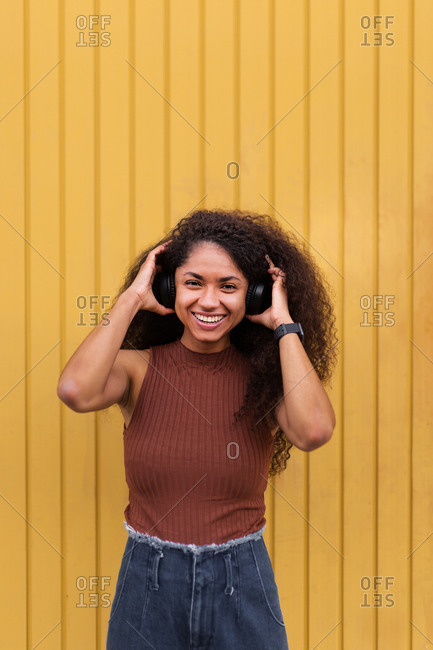 Lovely African American female with long curly hair and headphones in city and looking at camera