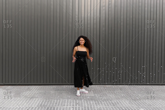 Joyful African American female with curly hair scattering white confetti in city while having fun and looking at camera