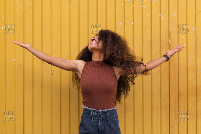 Joyful African American female with curly hair scattering white confetti in city while having fun and looking up