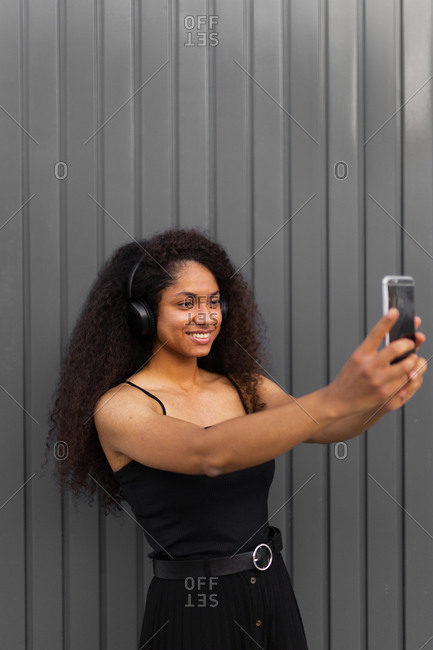 Positive ethnic female with Afro hairstyle standing in city and enjoying sound and songs in wireless headphones and taking selfie