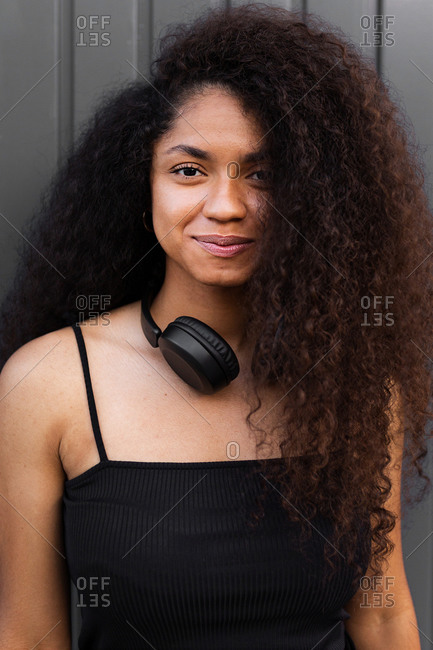 Lovely African American female with long curly hair and headphones on neck standing in city and looking at camera