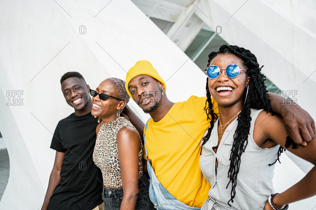Group of cheerful African American stylish people standing together on the street looking at camera