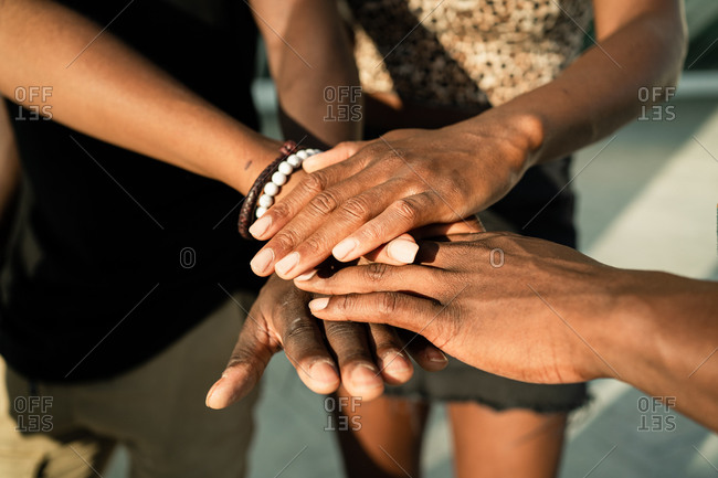 High angle of crop unrecognizable African American company of friends stacking hands together on street on sunny day