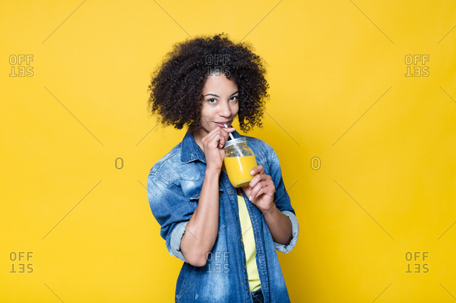 Cheerful young curly haired African American female in casual outfit looking at camera friendly and drinking fresh orange juice while standing against yellow background