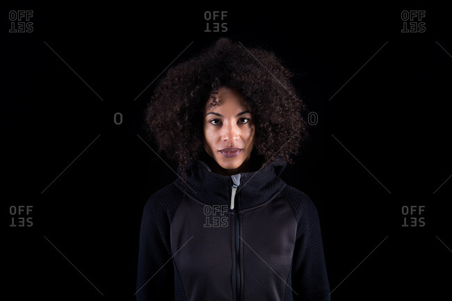 Young African American female with curly hair wearing black clothes looking at camera while standing against black background