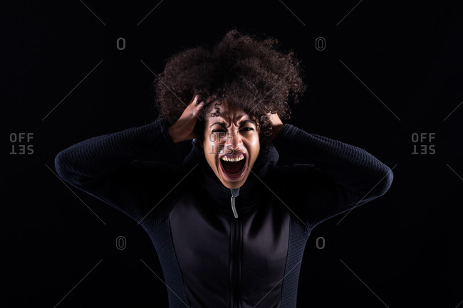 Stressful angry young African American female with curly hair shouting loudly and touching head while standing against black background