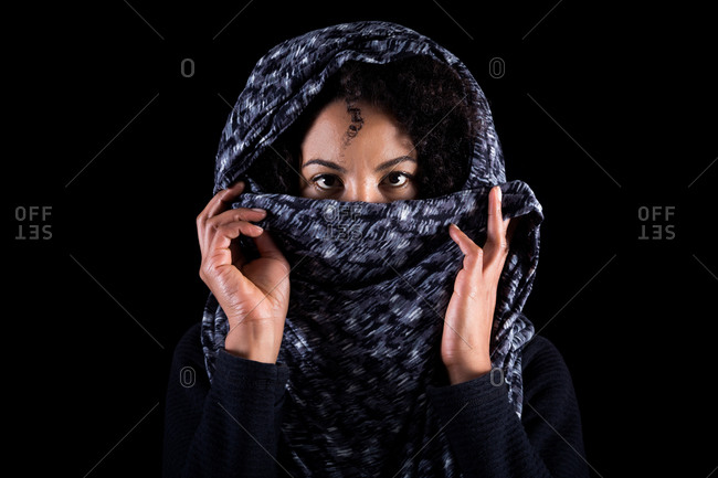 Serious young black female hiding half face with headscarf and looking at camera against dark background