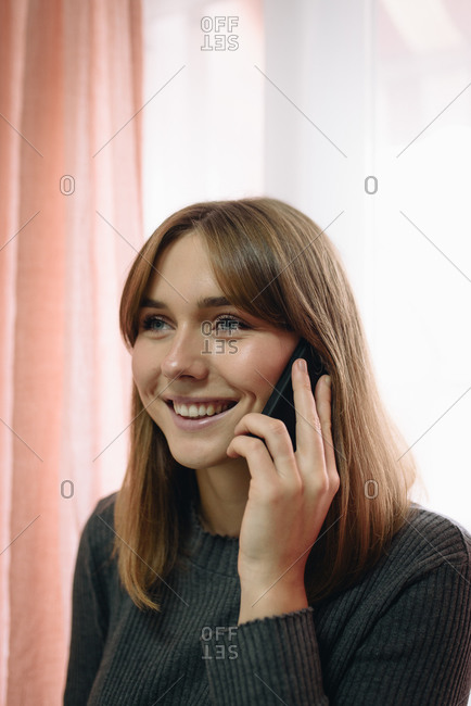 Blonde girl using a mobile phone at home