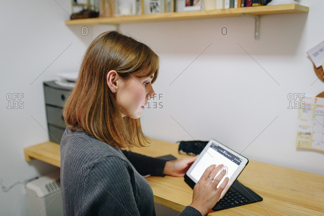Blonde girl sitting at a desk at home looking at a tablet