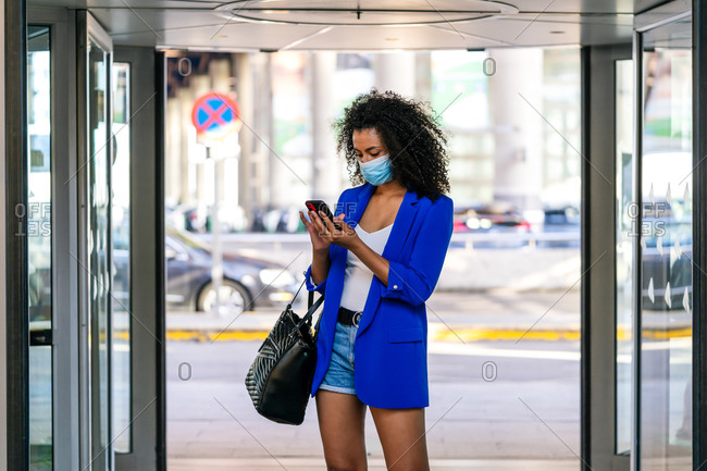 Young African American female in mask and with curly hair standing near entrance of shopping mall and browsing smartphone during coronavirus epidemic