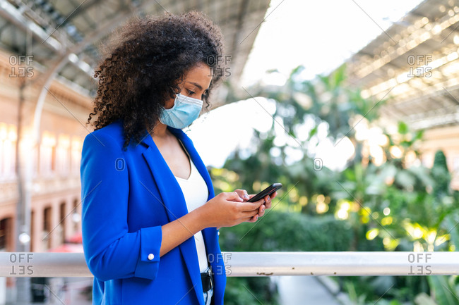 Side view of African American female in medical mask standing on bridge in botanic garden and browsing mobile phone during coronavirus