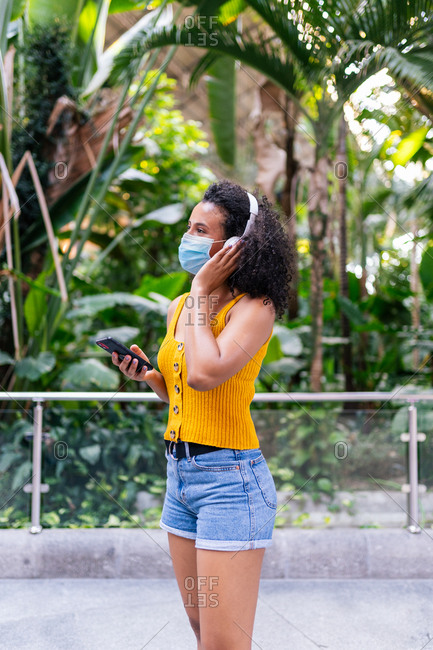 Side view of carefree happy ethnic female wearing face mask in headphones listening to music on mobile phone in green park during coronavirus pandemic