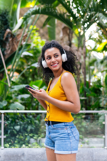 Side view of carefree ethnic female in headphones listening to music on mobile phone in green park while looking away and smiling