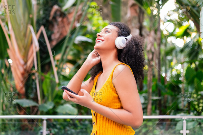 Side view of carefree ethnic female in headphones listening to music on mobile phone in green park while looking up and smiling