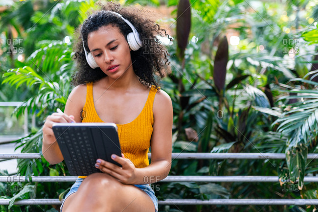 African American female in headphones sitting on bench and browsing tablet with stylus