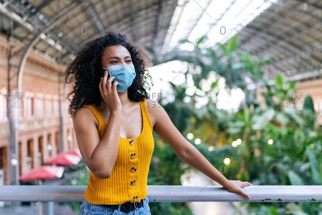 African American female in medical mask standing on bridge in botanic garden speaking on mobile phone during coronavirus looking away