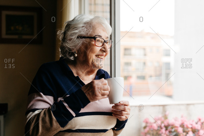 Side view of smiling elderly female standing near window with cup of coffee and enjoying morning at home