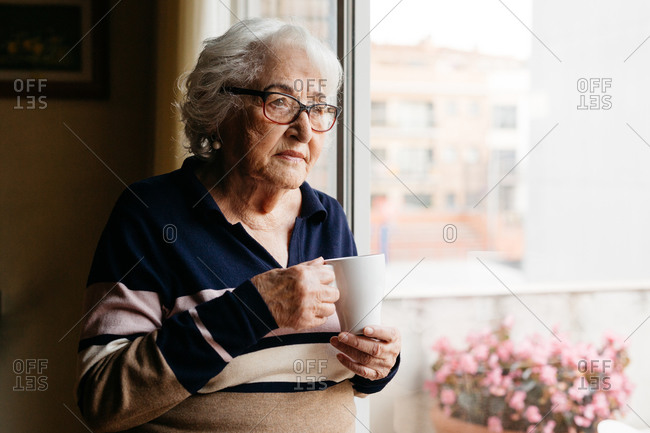 Side view of elderly female standing near window with cup of coffee and enjoying morning at home