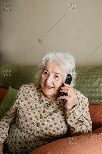 Smiling senior female sitting on comfortable couch and speaking on mobile phone with friend while looking away