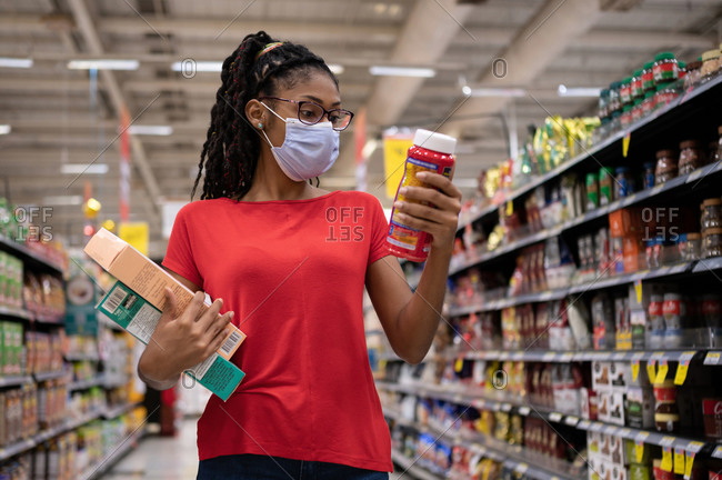 Afro latina young woman wearing a face mask walks aisle and looks at products while shopping in supermarket