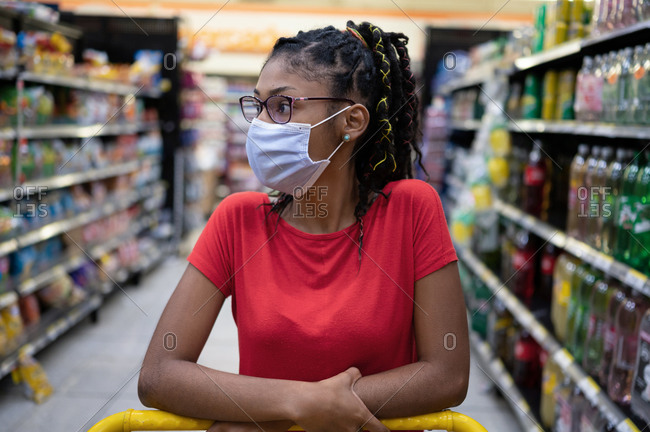 Afro latina young woman wearing a face mask pushes shopping cart through supermarket aisle