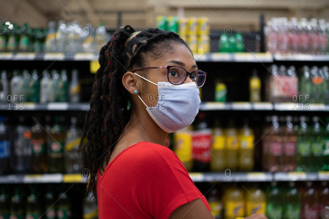 Afro latina young woman wearing a face mask looks at products in beverage aisle while shopping in supermarket