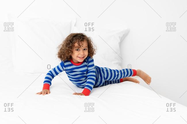 Smiling toddler boy playing on white bed