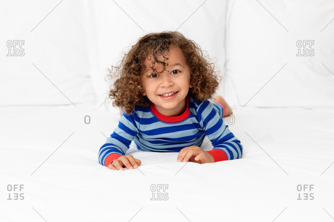 Smiling toddler boy lying on white bed
