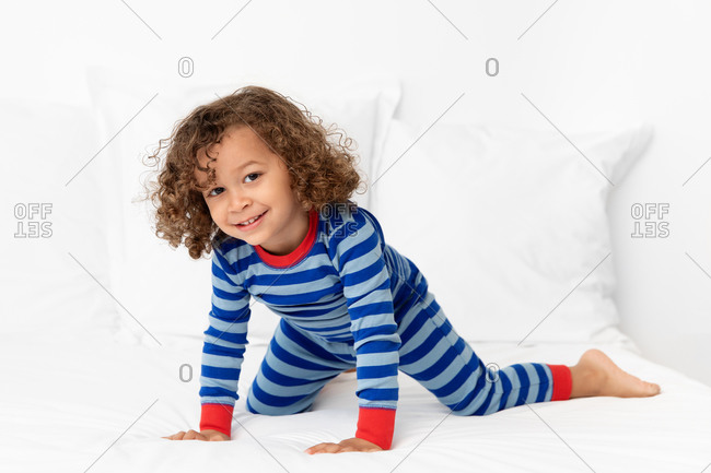Happy toddler boy crawling on white bed