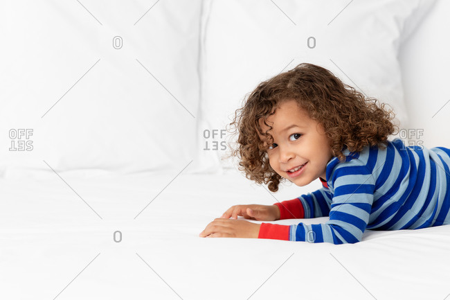 Portrait of happy young boy lying on white bed